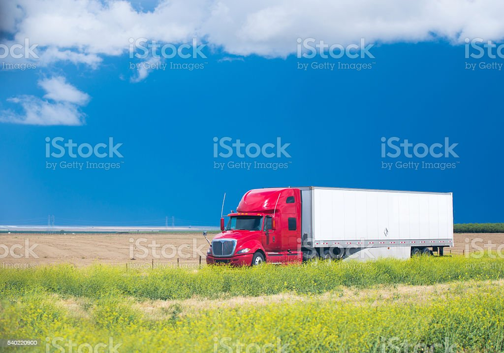 Red Semi Truck on the road in the middle of the field stock photo