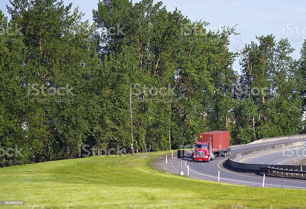 Rosso semi-camion con container sull'autostrada all'uscita foto stock royalty-free