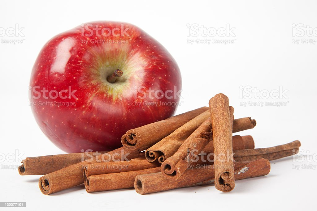 Red shiny apple and cinnamon against white background stock photo