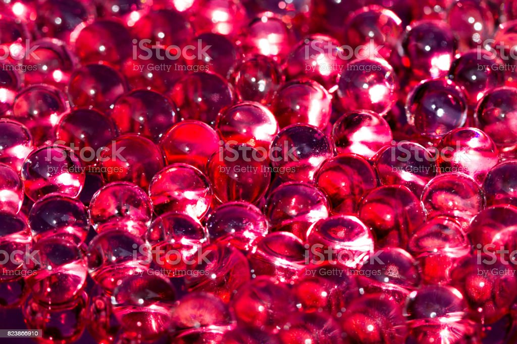 Red shiny water gel balls. Macro photo, can be used both for advertising or cosmetics, jewellery and for medicine. Abstract background. stock photo