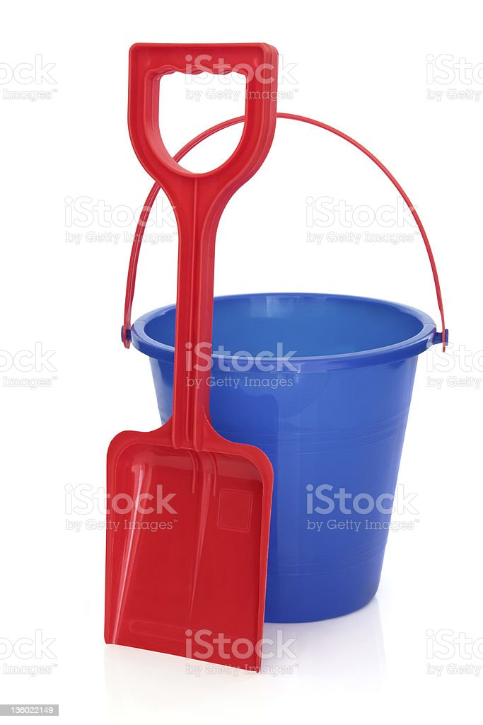 Red shovel and a blue pail beach toys on a white background stock photo