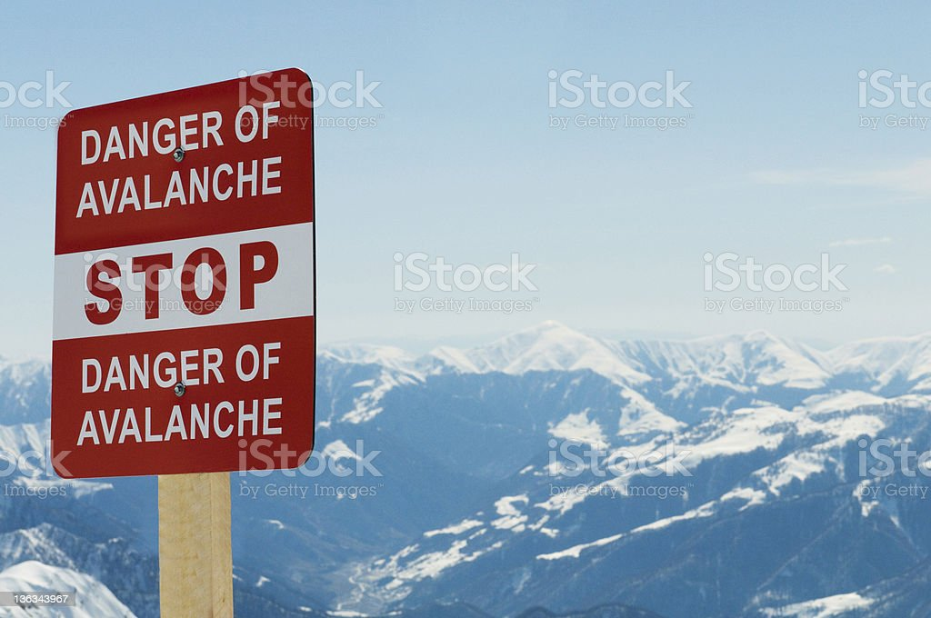 A red sign warning of an avalanche on a mountainous backdrop stock photo