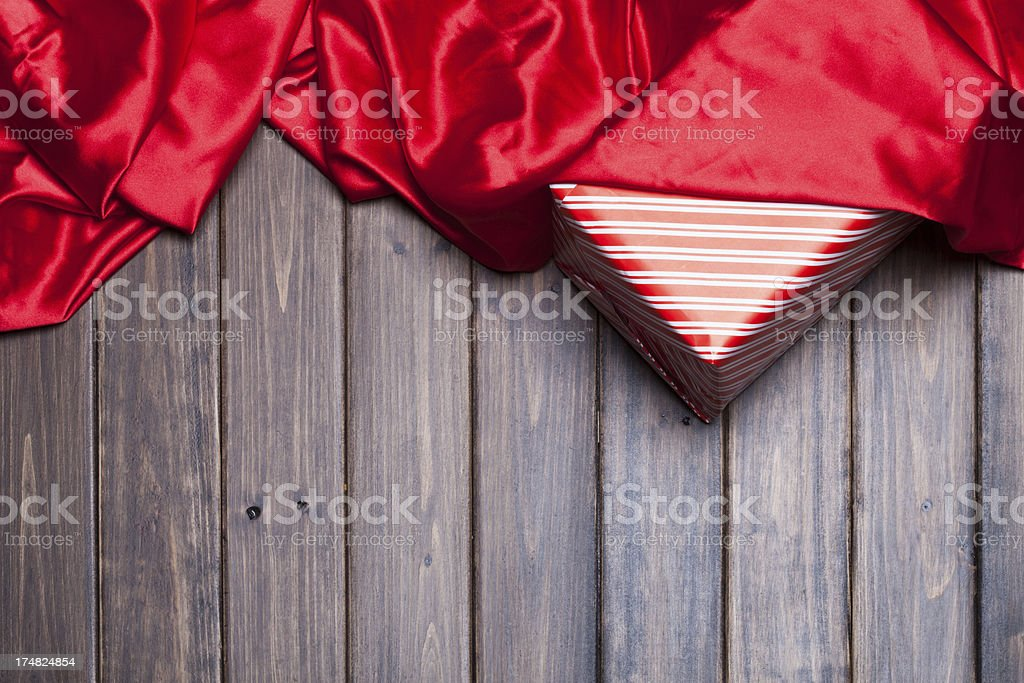 red silk over gift on wooden background stock photo