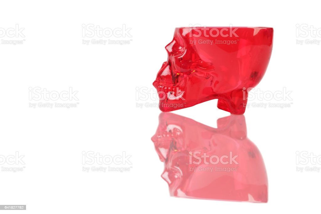 red skull and whiskey on white table stock photo