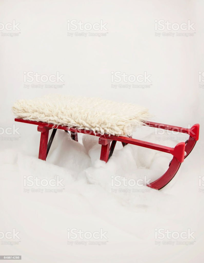 Red Sledge on fake snow, with sheepskin on top. stock photo