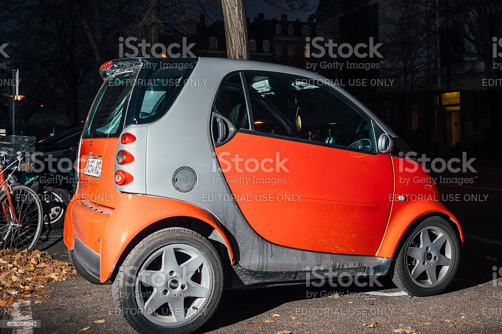 Red Smart for to car parked in city at night stock photo