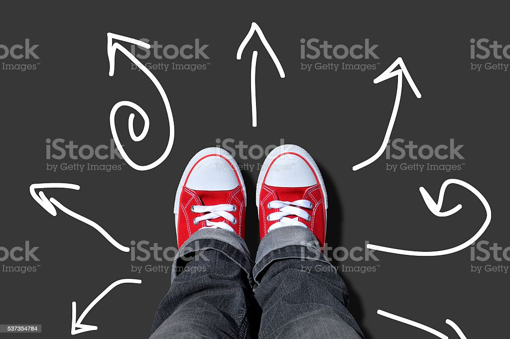 red sneakers on multi-directional arrows stock photo