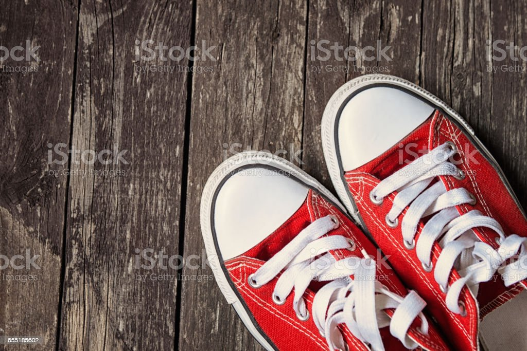 red sneakers on wooden background.Toned image stock photo