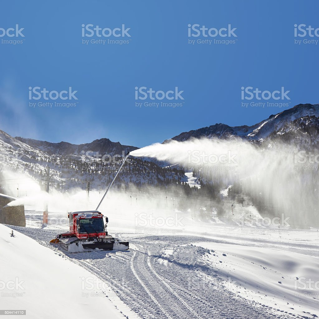 Red snow groomer and snow canon in the mountain stock photo