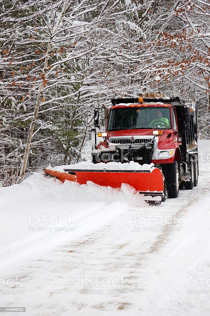 Red snow plow working a snow bank stock photo