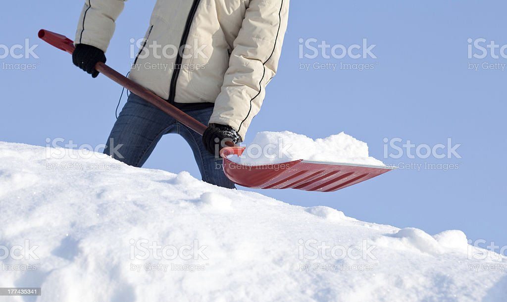 A red snow shovel is used to remove snow on a sunny day stock photo