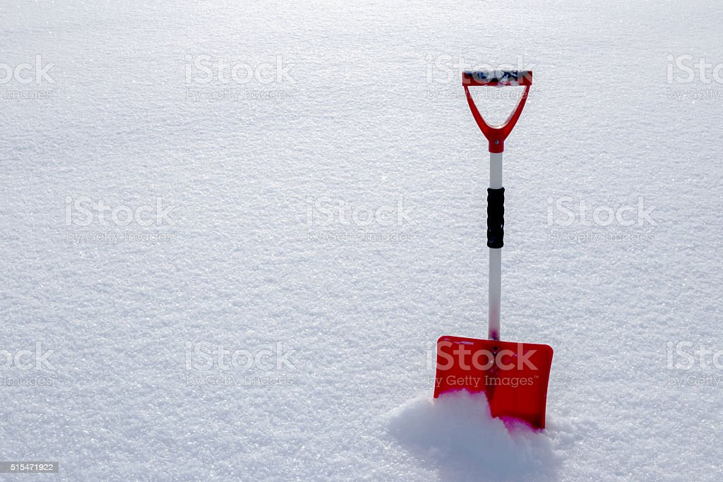 Red snow shovel standing in the snow stock photo
