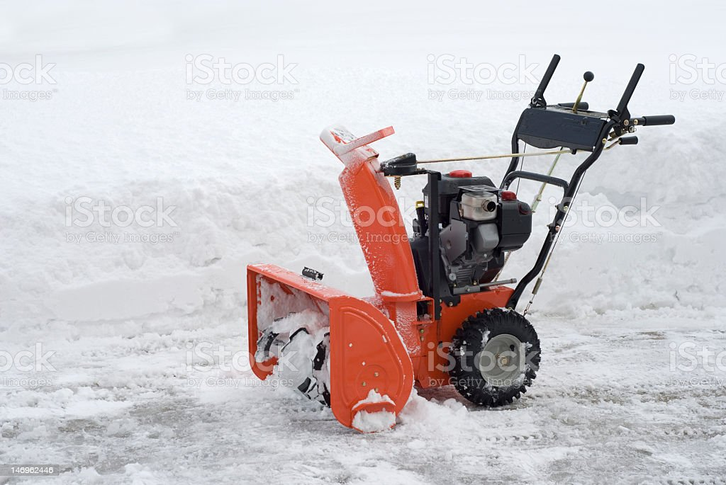 Red snowblower on a road beside white snow stock photo