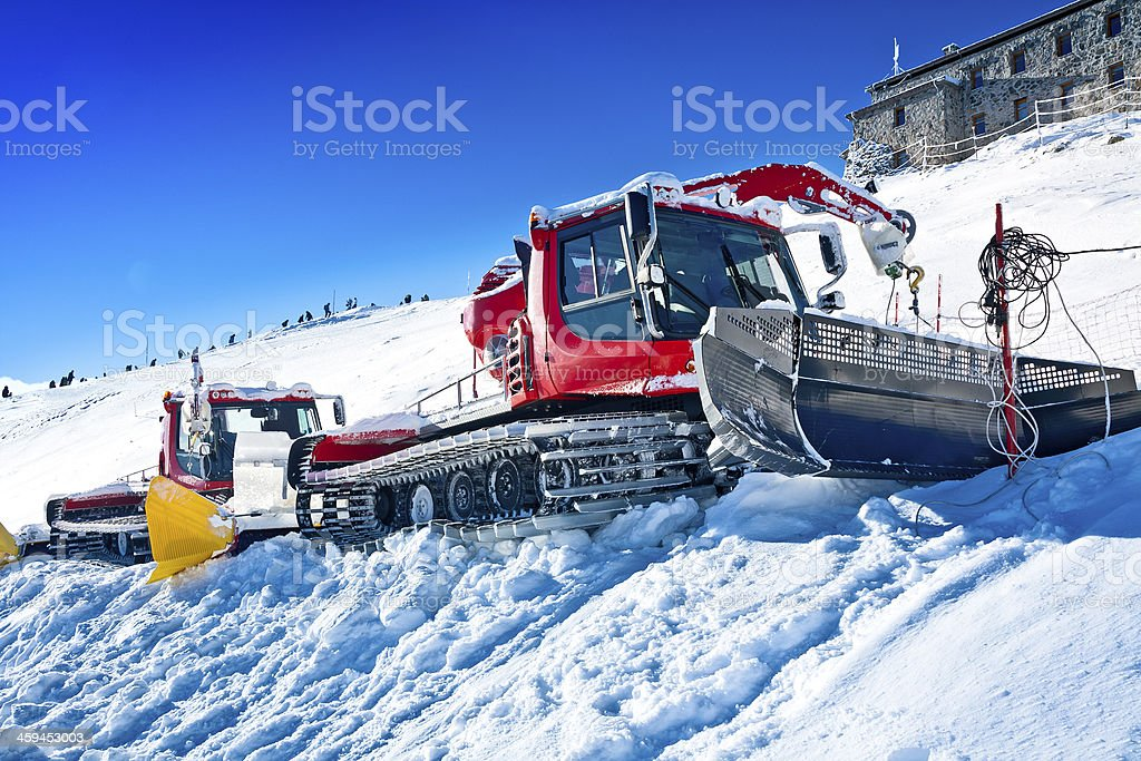 Red snowplow machines in ski station stock photo