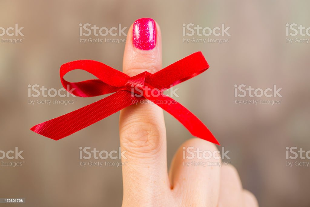 Red social awareness ribbon tied around index finger. Reminder. stock photo