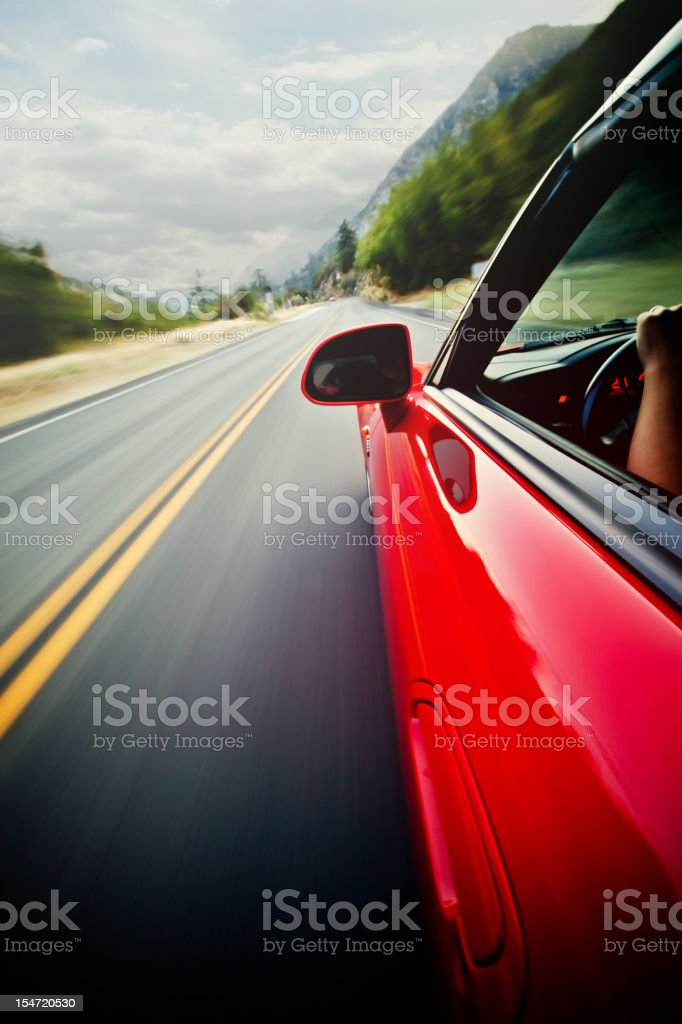 red sports car on the mountain road stock photo