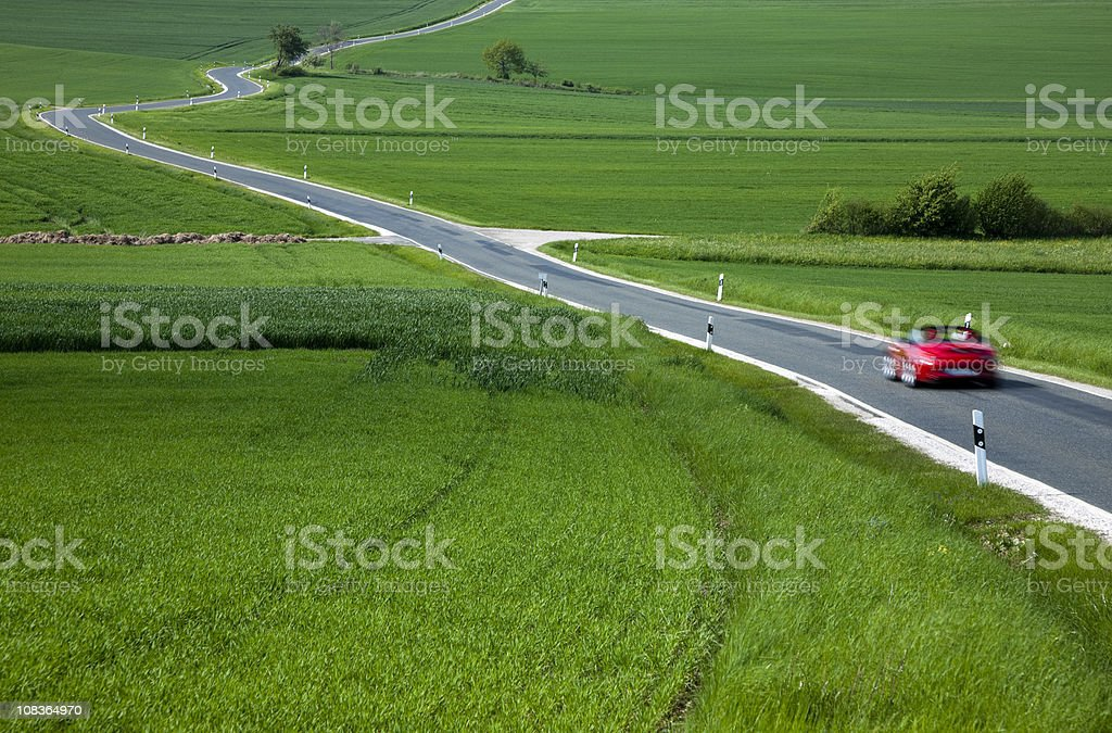 Red Sports Car Speeding on Rural Winding Road in Spring stock photo