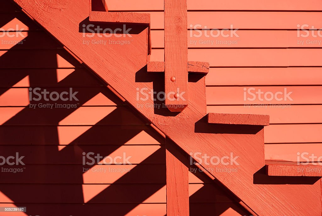 Red stairs of the red barn with shadows stock photo