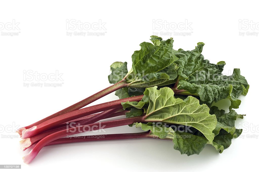 Red stems and green leaves of Rhubarb on a white surface stock photo