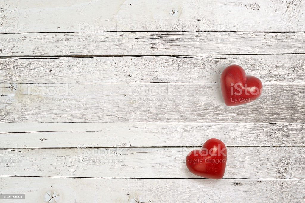 red stone hearts on a white wooden background stock photo