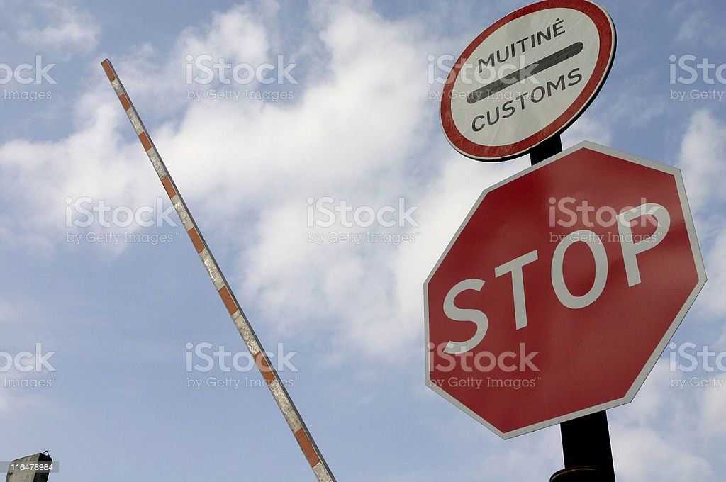 Red stop sign at the border between countries stock photo