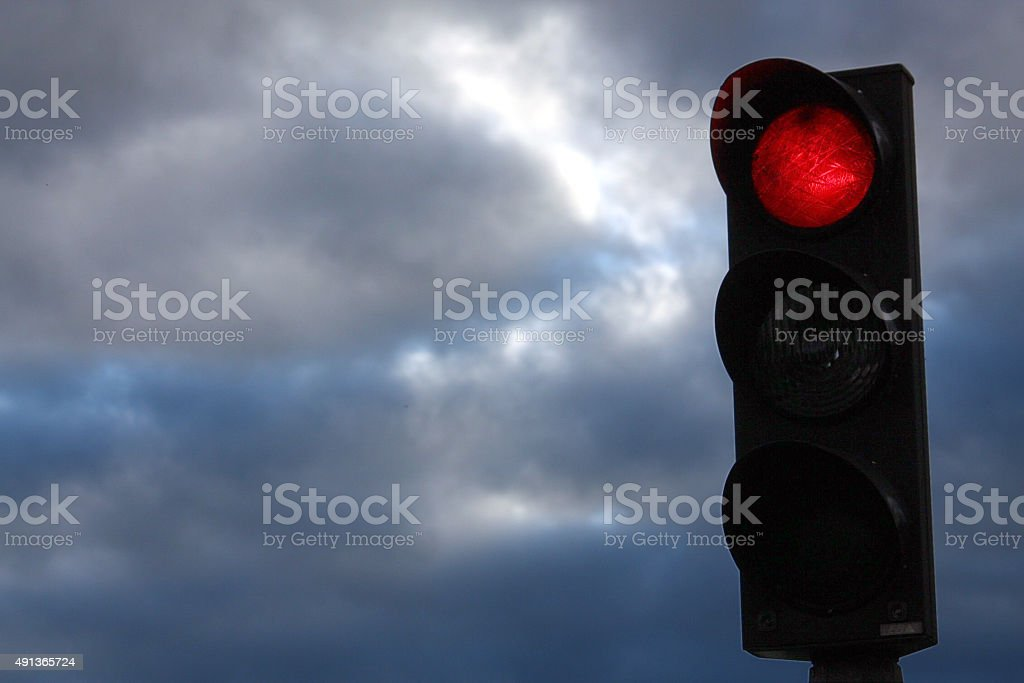 Red Stop trafficlight on dark skies stock photo