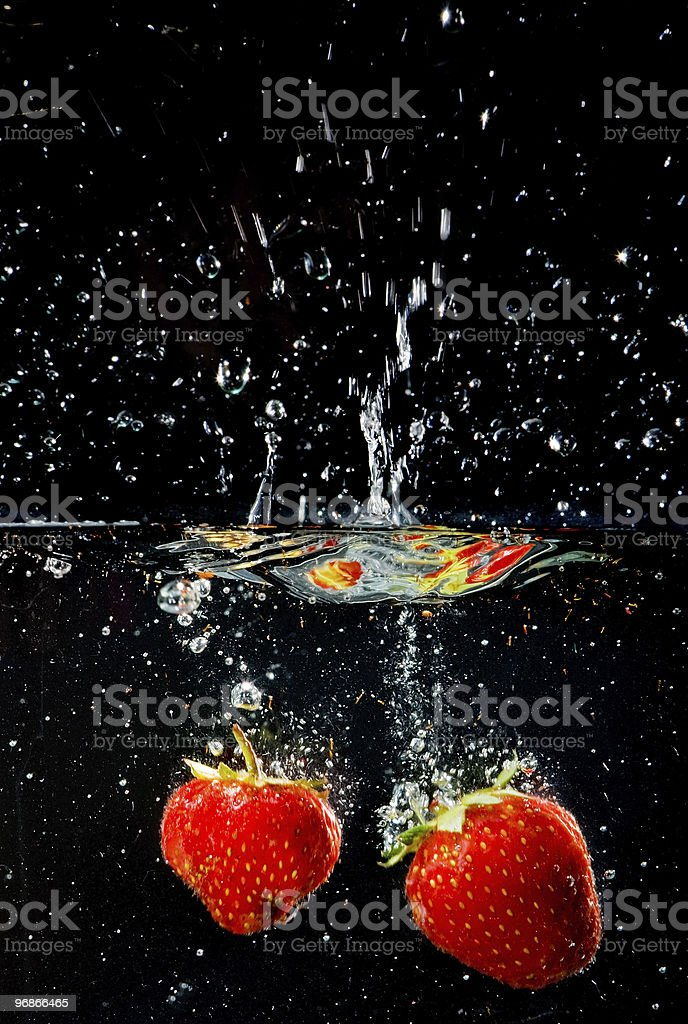 Red strawberries underwater at the black background. stock photo