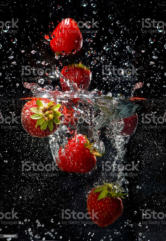 Red strawberries underwater at the black background. royalty-free stock photo