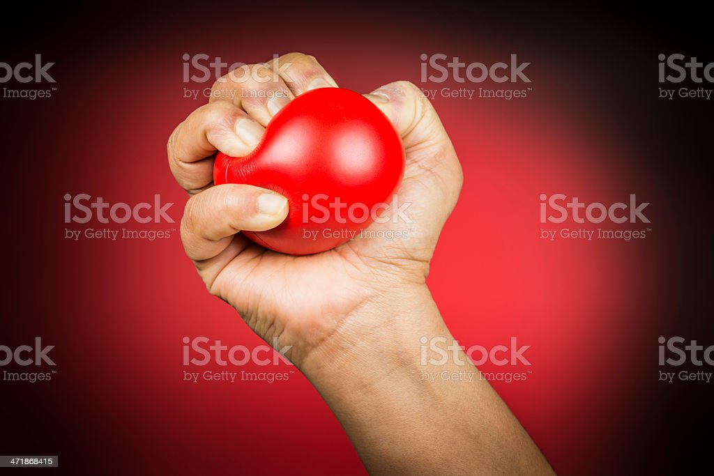 Red stress ball in hand stock photo