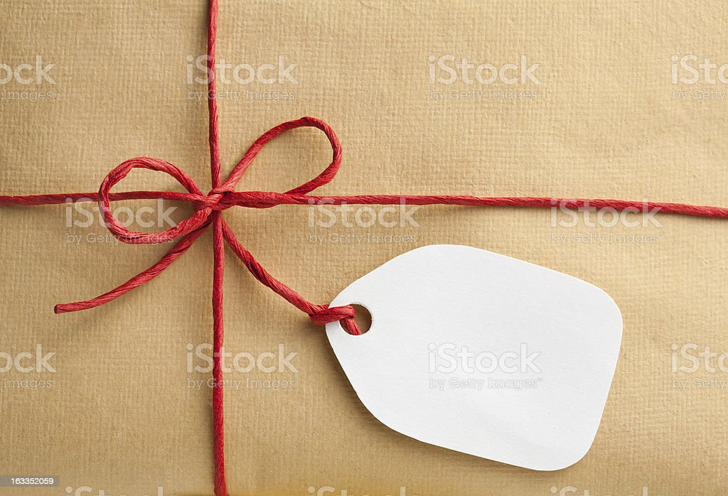 Red string and blank label, brown paper as background stock photo