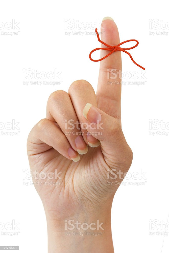 Red string bow tied on index finger stock photo