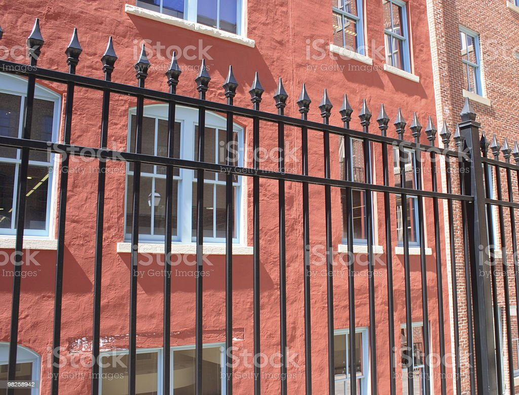 red stucco and black iron fence royalty-free stock photo