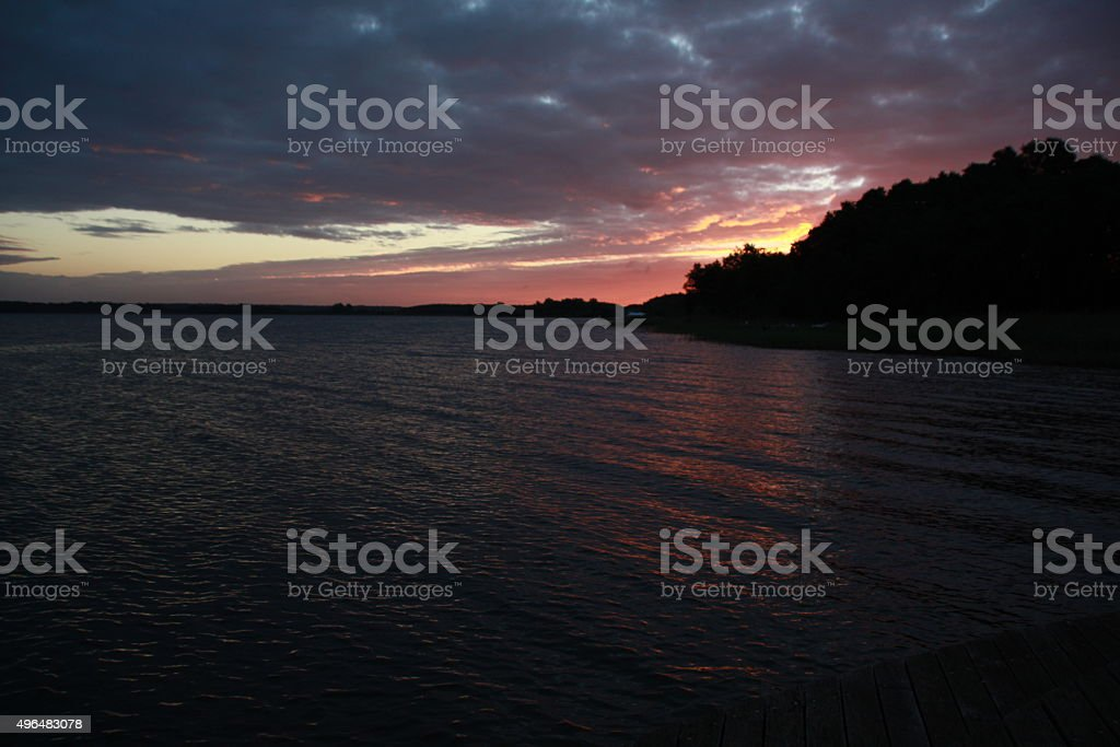 red sunrise between water and clouds stock photo