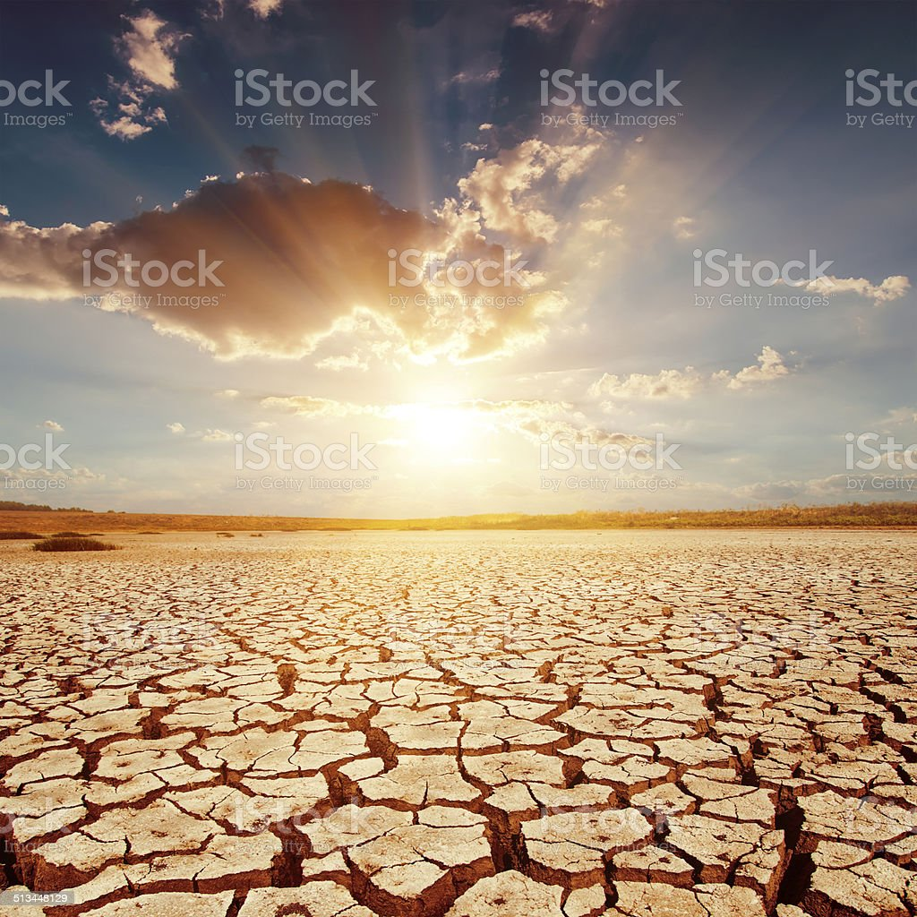 red sunset over cracked earth stock photo