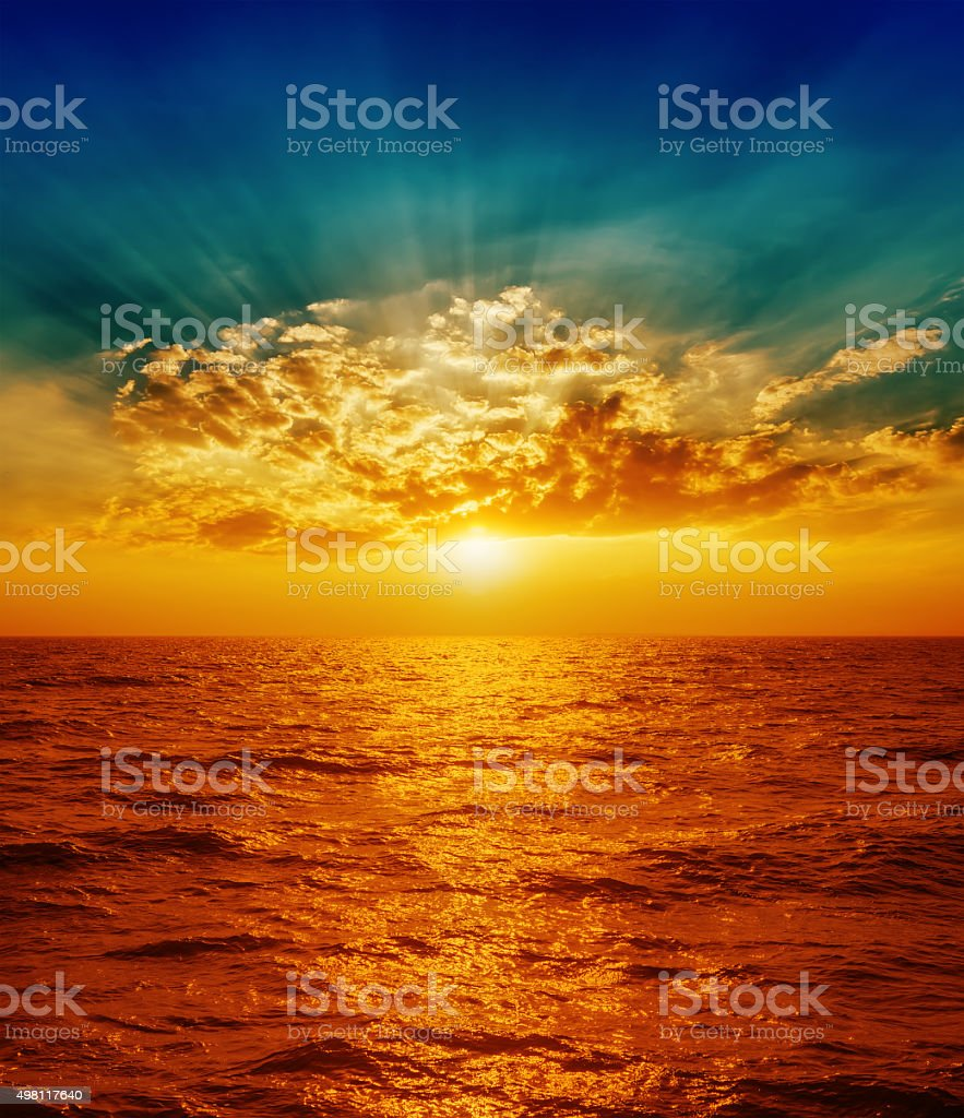 red sunset over sea in clouds stock photo