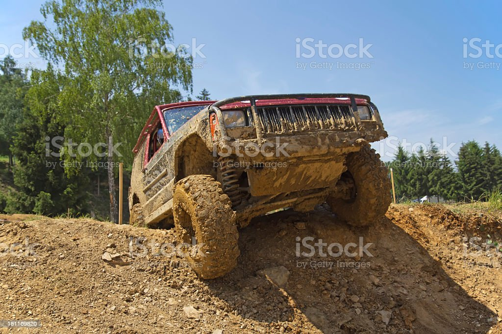 Red SUV overcomes steep muddy slope. royalty-free stock photo