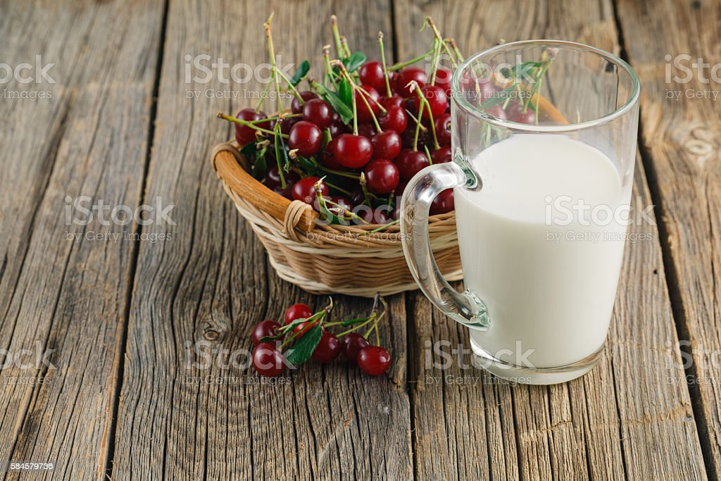 Red sweet cherries with glass of milk stock photo