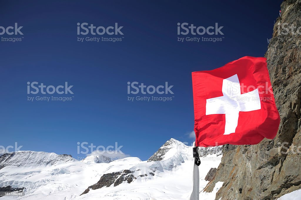 Red Swiss Flag Flying with Mountain Background royalty-free stock photo