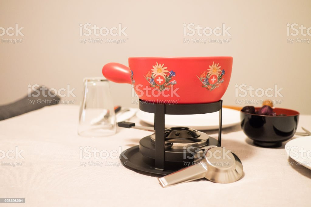 Red Swiss fondue pot on a table stock photo