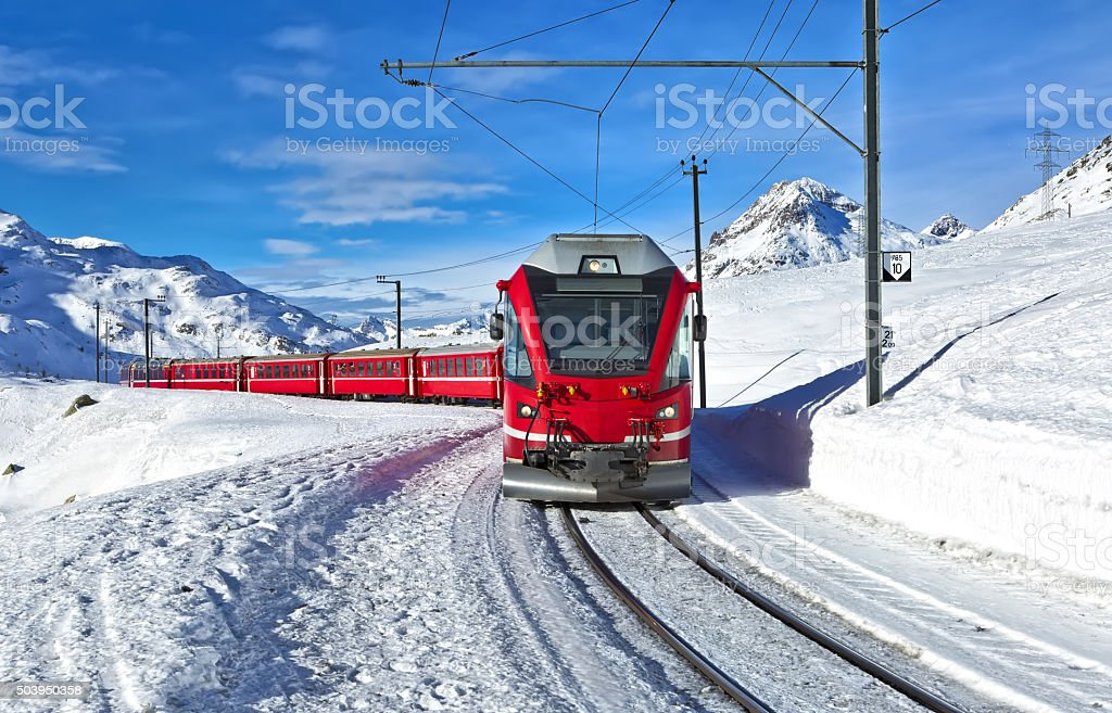Red swiss train running through the snow stock photo