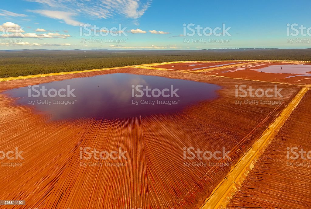 Red Tailing Pond under Blue Sky stock photo