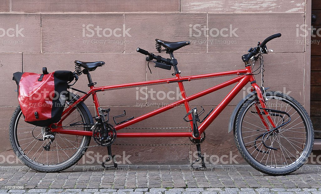 Red tandem bicycle leaning on a wall stock photo