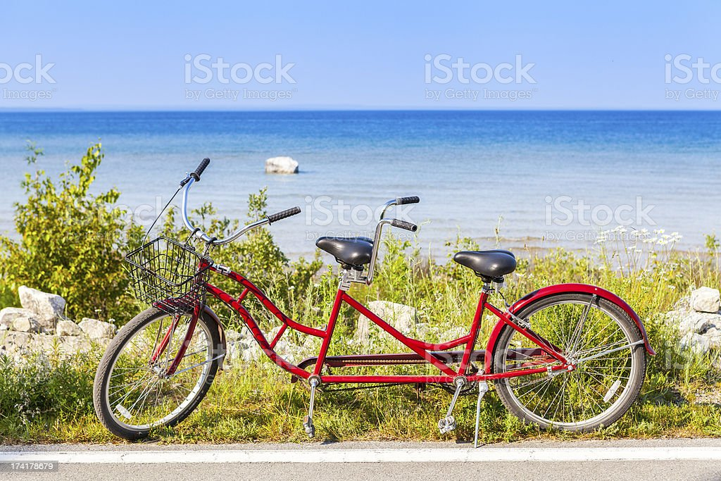 Red tandem bicycle on the side of a road by a beach stock photo