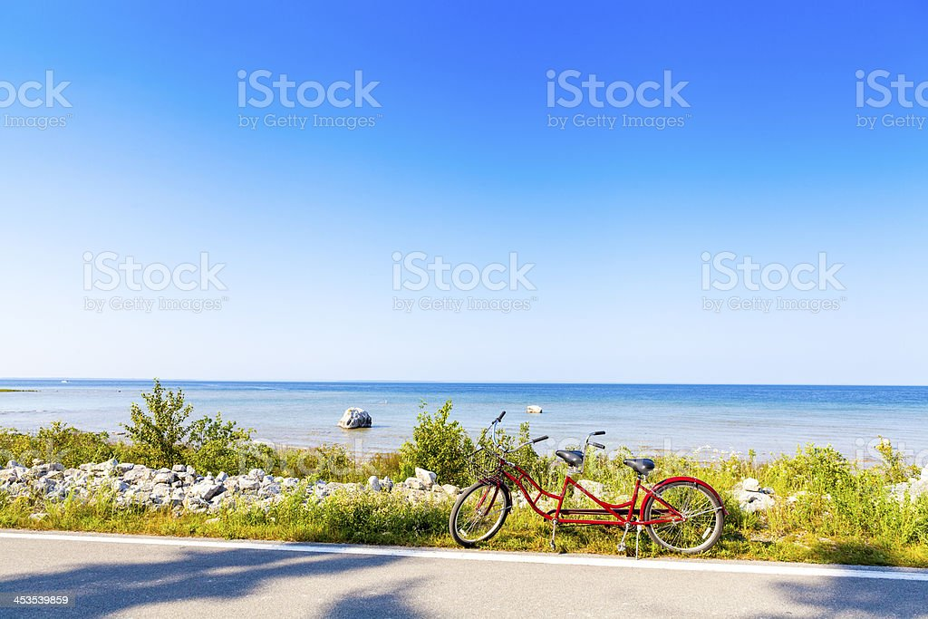A red tandem bike parked on a beach road stock photo
