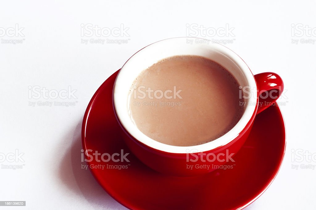 Red tea cup with saucer on table against white background royalty-free stock photo