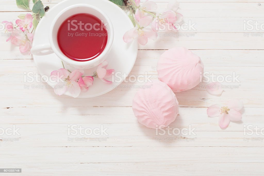 Red tea with flowers on white wooden background stock photo