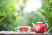 Red teapot white cup whit heart pattern on wooden table