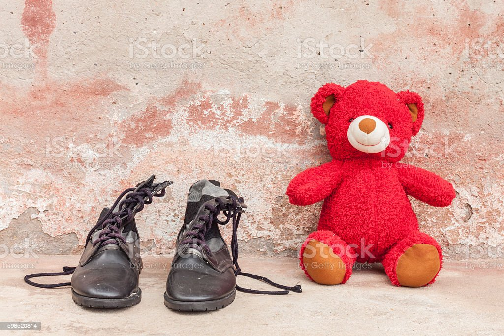 red teddy bear with combat boots on cement wall stock photo