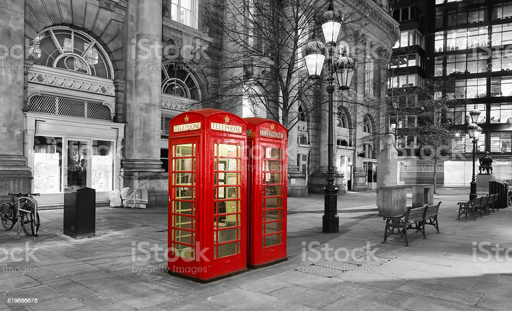 Red telephone booth in the City of London by night stock photo