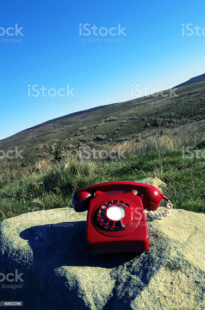 red telephone on a rock, hillside. stock photo